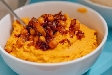 Image depicting a bowl of red pepper hummus garnished with roast chickpeas and onions. Image used as link to more information about our catering services